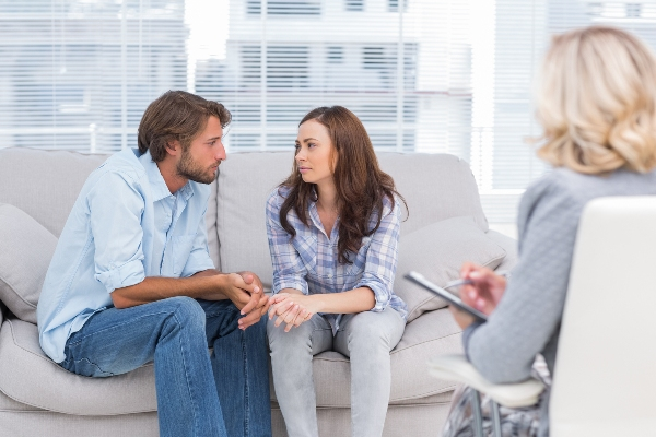 Couple looking to each other during therapy session while therapist watches