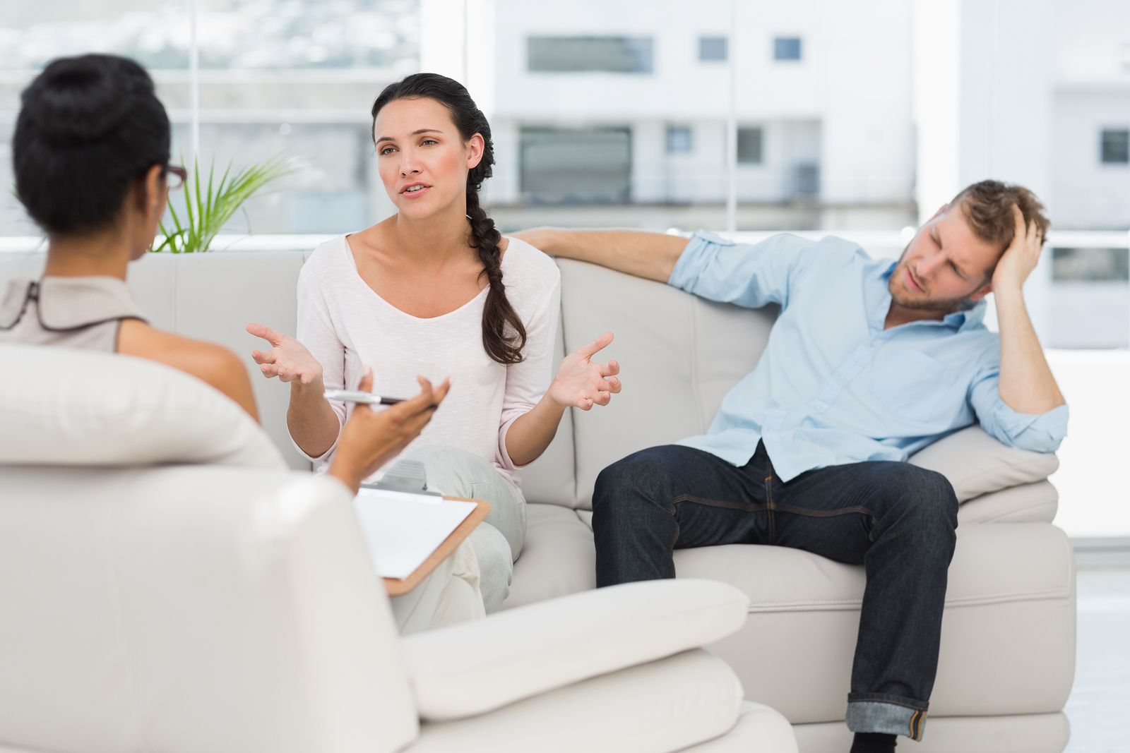 Angry couple sitting on couch talking to therapist in therapists