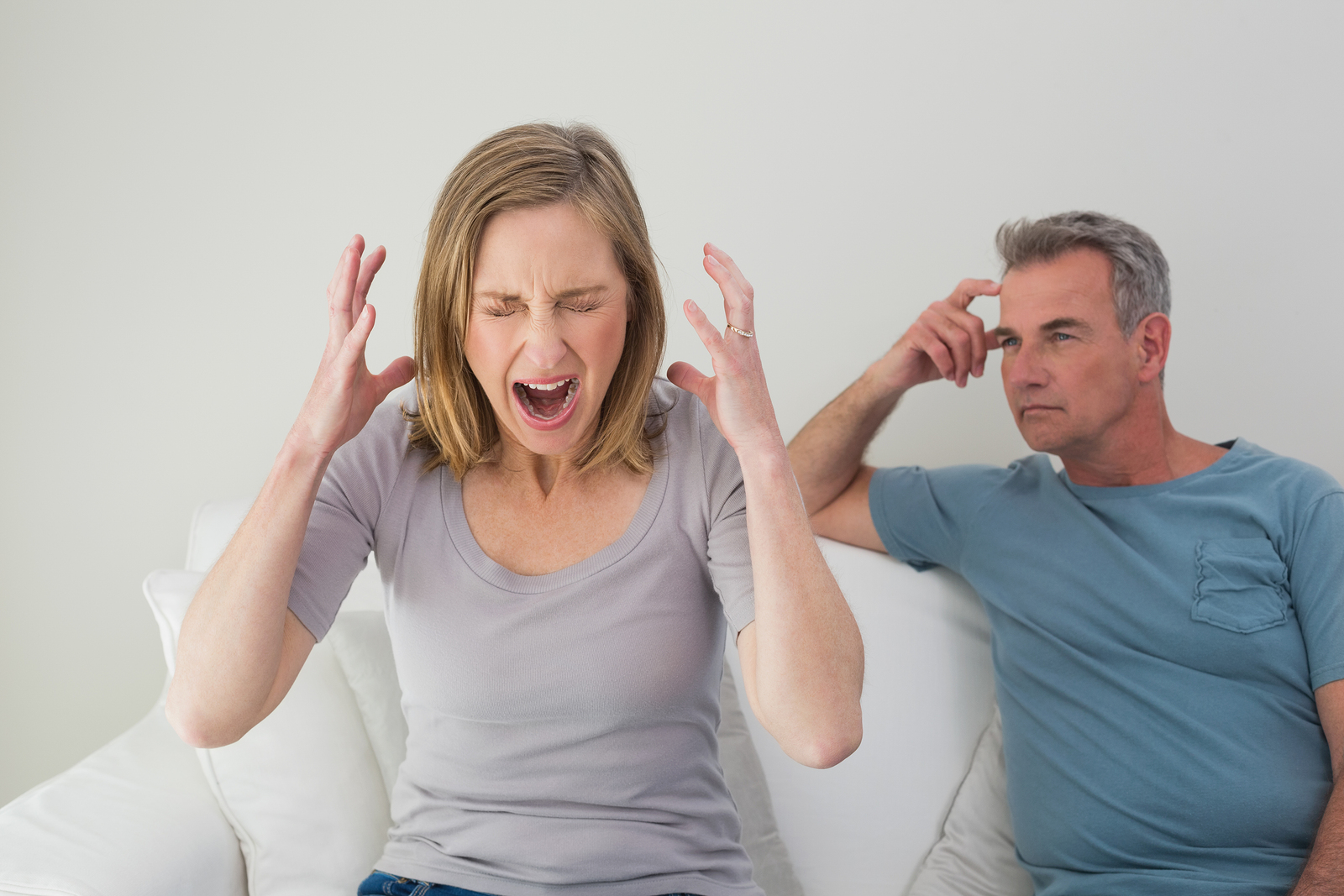 Unhappy couple having an argument in the living room at home